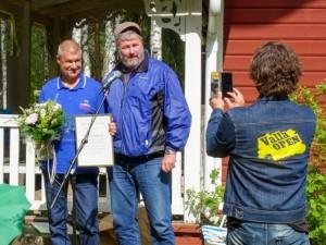 Jonny Mill, ordförande i samhällsutvecklings-utskottet delar ut kommunens kulturstipendium till Järvsö Bollklubb, här representerad av Kent Skalberg, för deras danser i Nor